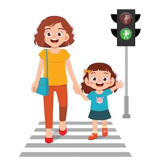 Szczęśliwa śliczna małe dziecko dziewczyna krzyżuje drogę z matką