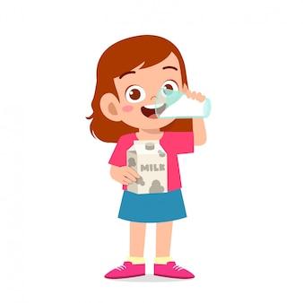 Szczęśliwa śliczna małe dziecko dziewczyna pije mleko