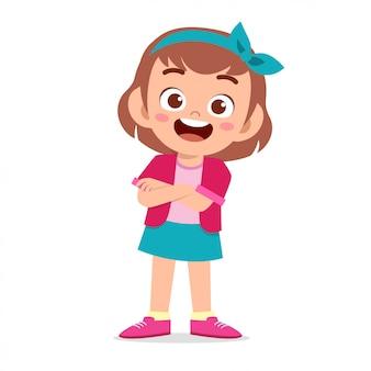 Szczęśliwa śliczna uśmiechu dzieciaka dziewczyna krzyżował ręki