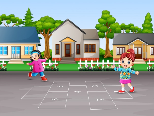 Szczęśliwe dzieci bawiące się gra w klasy na podwórku