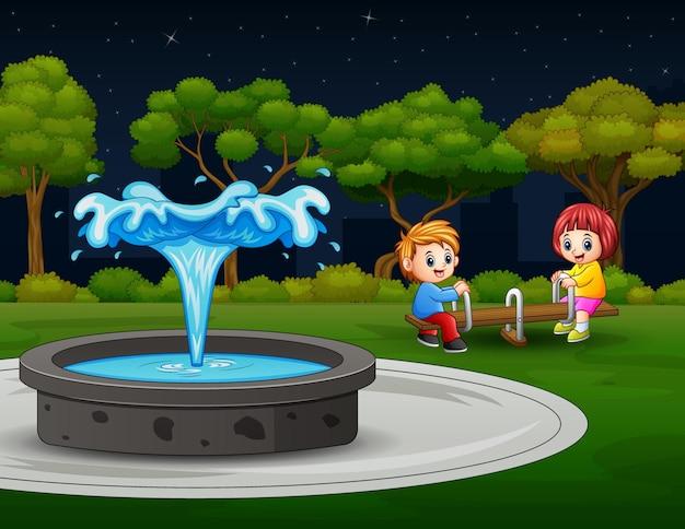 Szczęśliwe dzieci bawiące się na huśtawce w pobliżu fontanny