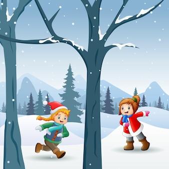 Szczęśliwe dzieci bawiące się na świeżym powietrzu w zimie