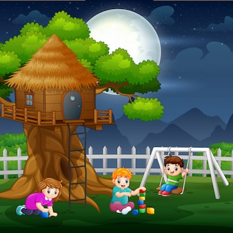 Szczęśliwe dzieci bawiące się wokół domku na drzewie w nocy