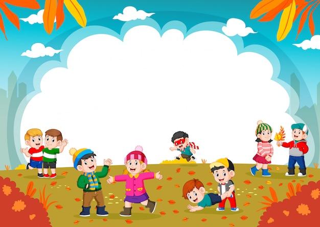 Szczęśliwe dzieci bawiące się z liści jesienią