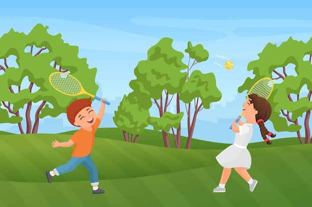 Szczęśliwe dzieci grają w badmintona w letnim parku krajobraz dziewczyna chłopiec dziecko trzyma rakiety