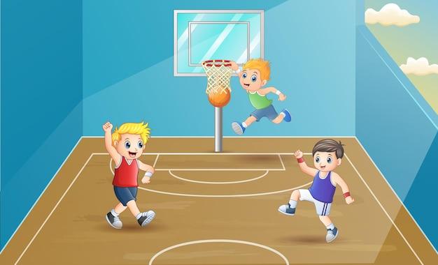 Szczęśliwe dzieci grające w koszykówkę w hali sportowej