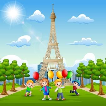 Szczęśliwe dzieci przynoszą balony przed wieżą eiffla