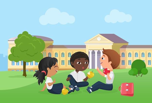 Szczęśliwe dzieci spędzają wspólnie czas po lekcjach szkolnych siedząc na pikniku na trawniku