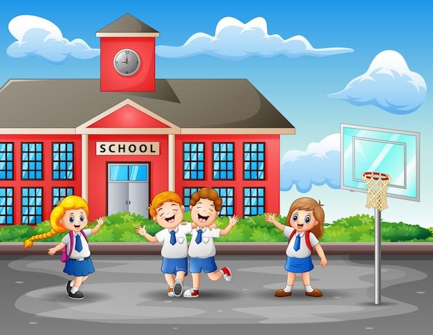 Szczęśliwe dzieci w mundurze na boisku do koszykówki