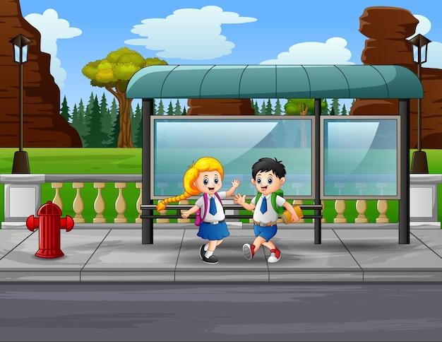 Szczęśliwe dzieci w wieku szkolnym na ilustracji przystanku autobusowego