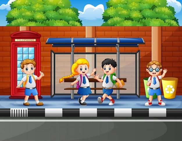 Szczęśliwe dzieci w wieku szkolnym na przystanku autobusowym