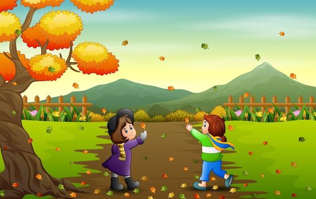 Szczęśliwe dziewczyny łapią spadający liść w jesienny krajobraz