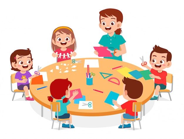 Szczęśliwe śliczne małe dzieci chłopiec i dziewczynka robią papierowe rzemiosło z nauczycielem