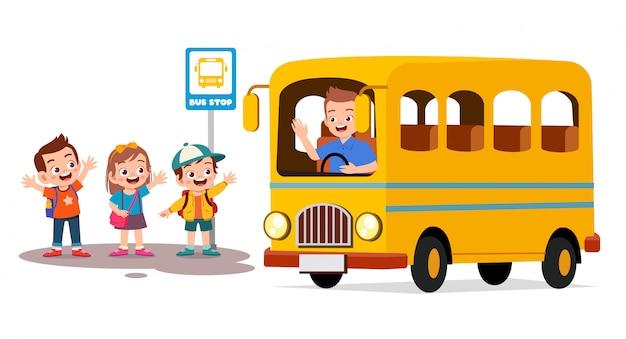 Szczęśliwe słodkie dzieci czekają szkolny autobus z przyjaciółmi