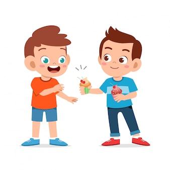 Szczęśliwe słodkie dzieci jeść babeczki
