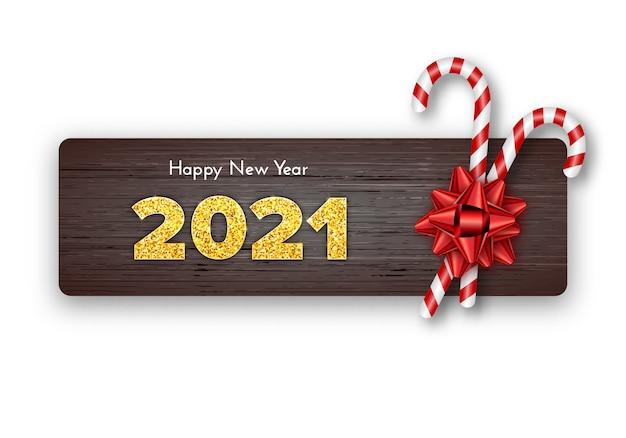 Szczęśliwego nowego roku karty 2021. wakacyjne cukierki laski i czerwona kokarda na tle drewna