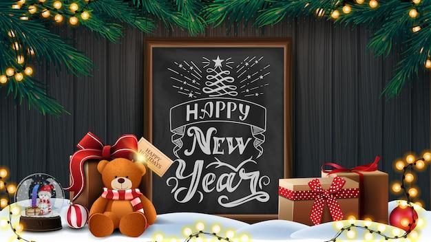 Szczęśliwego nowego roku z drewnianą ścianą, gałęzi choinki, wianek, tablica kredowa z napisem i prezenty