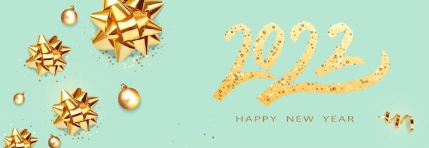 Szczęśliwego nowego roku złoty tekst z jasnymi błyszczącymi złotymi kokardkami i kulkami