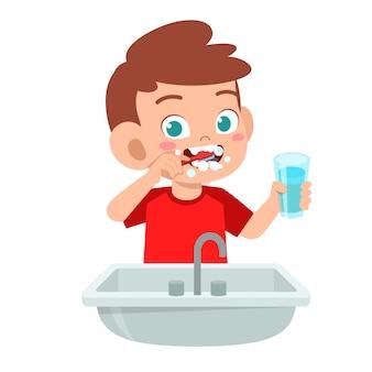 Szczęśliwego ślicznego dzieciaka chłopiec muśnięcia czyści zęby