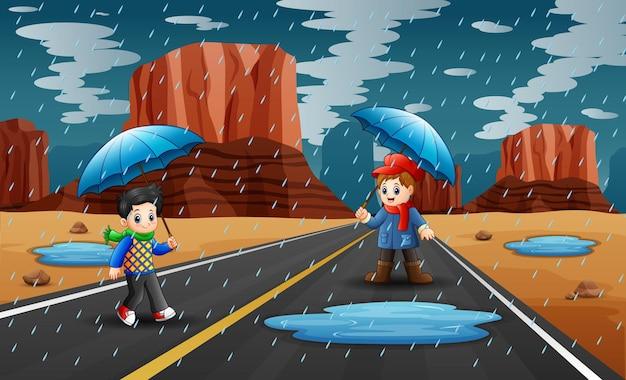Szczęśliwi chłopcy trzymając parasol w deszczu na drodze