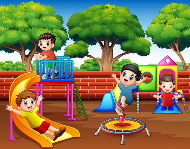 Szczęśliwi dzieci bawić się w boisku przy dniem
