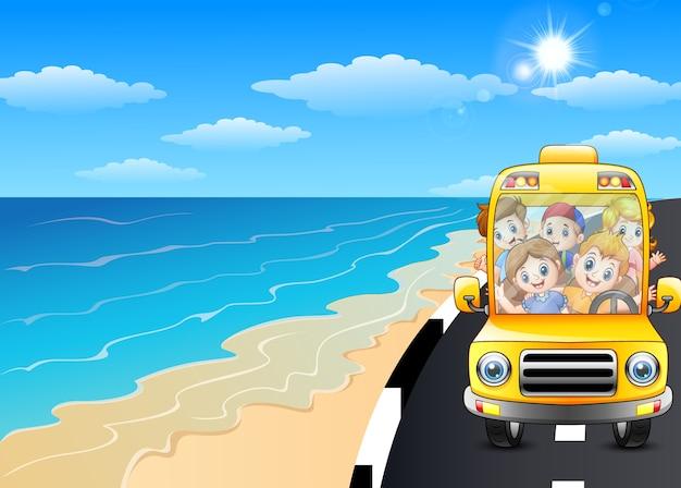 Szczęśliwi dzieci jedzie samochód w nadmorski drodze