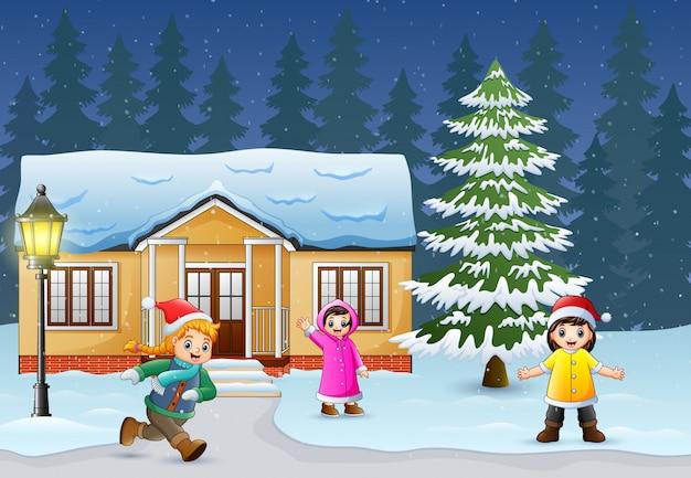Szczęśliwi dzieciaki bawić się przed snowing domem