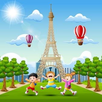 Szczęśliwi dzieciaki bawić się przed wieży eifla tłem