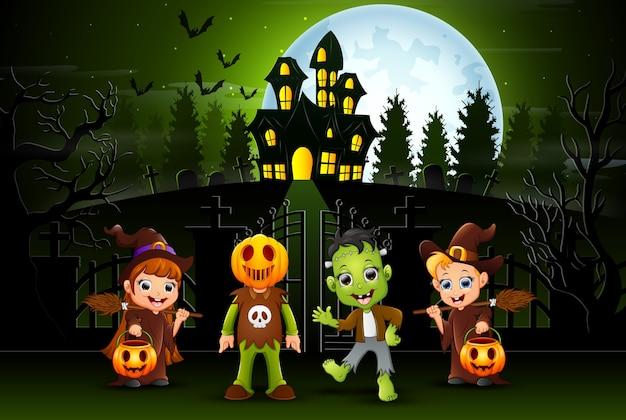 Szczęśliwi halloween dzieciaki outdoors z nawiedzającym domowym tłem