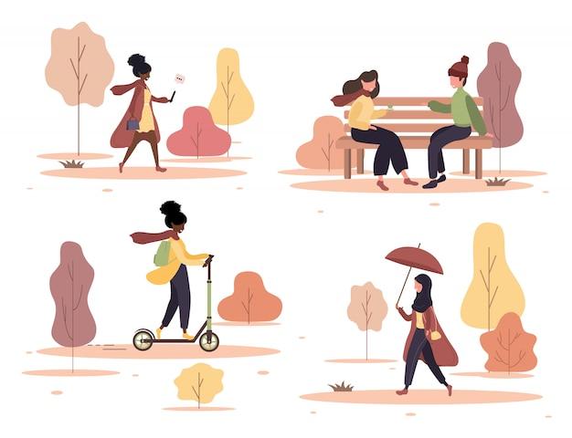 Szczęśliwi ludzie spacery zestaw jesienny park. młoda kobieta i mężczyzna siedzi na ławce i mówi. mieszkańcy spacerujący z parasolami, jeżdżący na hulajnodze. ilustracja w stylu cartoon płaski.