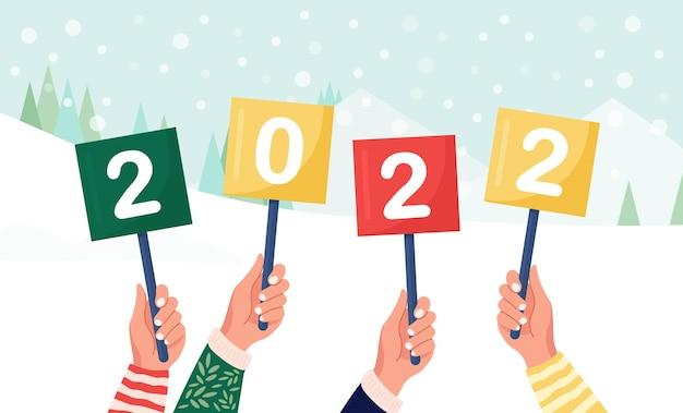 Szczęśliwi ludzie trzymają w rękach znaki lub afisz z numerami 2022. grupa przyjaciół życzy wesołych świąt i szczęśliwego nowego roku. pozdrowienia z wakacji. wesoli ludzie świętują boże narodzenie