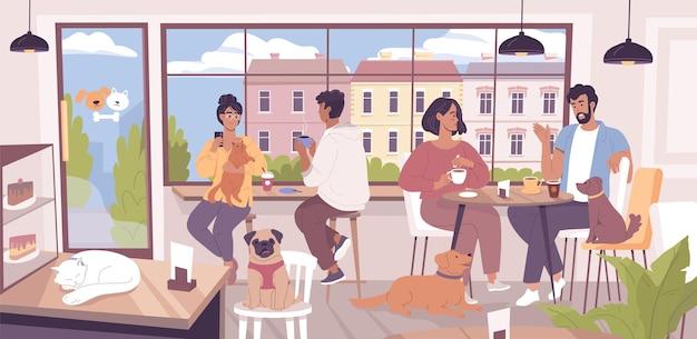 Szczęśliwi młodzi ludzie siedzący ze swoimi zabawnymi zwierzakami w nowoczesnej kawiarni przyjaznej zwierzętom