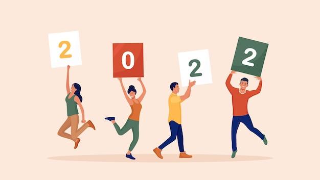 Szczęśliwi skaczący ludzie trzymają tabliczki lub tabliczki z numerami 2022. grupa przyjaciół życzy wesołych świąt i szczęśliwego nowego roku. pozdrowienia z wakacji. wesoli ludzie świętują boże narodzenie