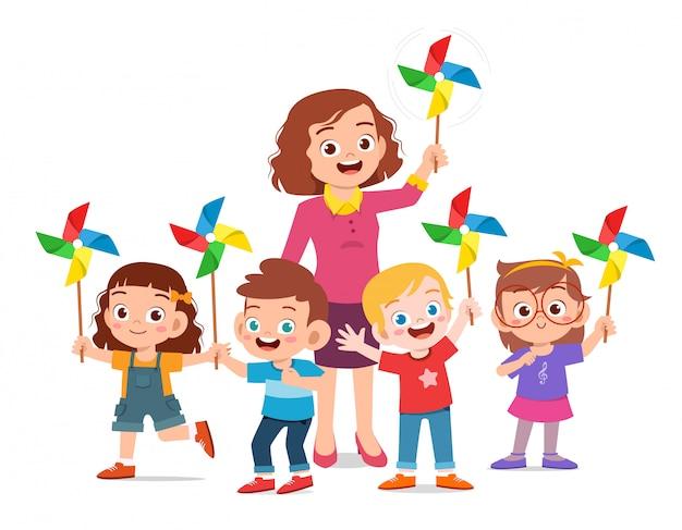 Szczęśliwi śliczni dzieciaki i nauczyciela mienia zabawka