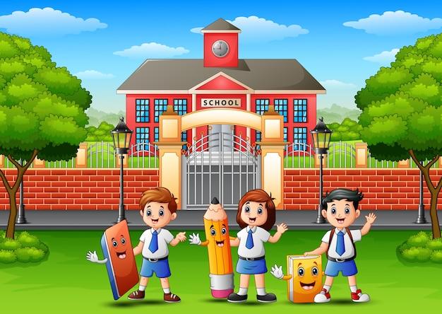 Szczęśliwi szkolni dzieci trzyma materiały przed szkolnym buildin