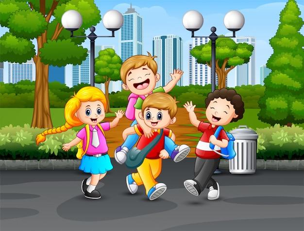 Szczęśliwi szkolni dzieciaki bawić się w parku