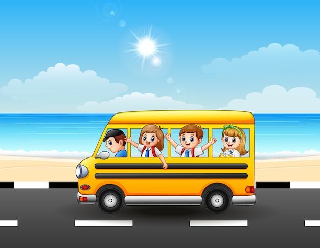 Szczęśliwi szkolni dzieciaki jedzie autobus szkolnego na nadmorskiej ulicie