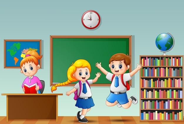 Szczęśliwi szkolni dzieciaki w mundurku szkolnym z żeńskim nauczycielem przy sala lekcyjną