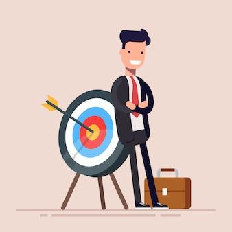 Szczęśliwy biznesmen lub kierownik stoi w pobliżu celu. strzała trafiła dokładnie w cel. płaskie ilustracja w stylu cartoon.