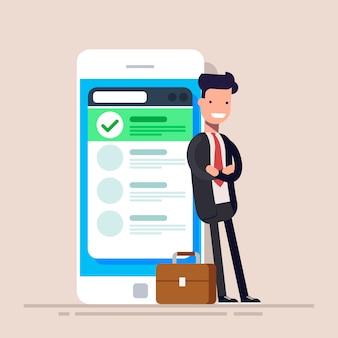 Szczęśliwy biznesmen lub kierownik stoi w pobliżu telefonu komórkowego z listą na ekranie.