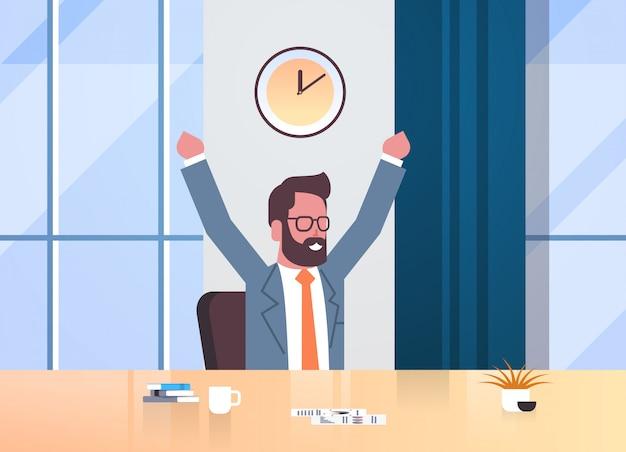 Szczęśliwy biznesmen podnosząc ręce wyrażając sukces skuteczne zarządzanie czasem koncepcja biznes człowiek siedzący miejsce pracy biurko nowoczesne biuro wnętrze mężczyzna postać z kreskówki portret poziome