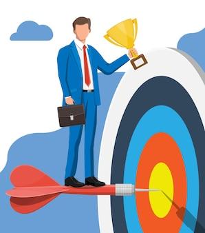 Szczęśliwy biznesmen z celem trofeum i strzałka. ustalanie celów. biznesmen z teczką. inteligentny cel. koncepcja biznesowa cel. osiągnięcie i sukces. ilustracja wektorowa w stylu płaski