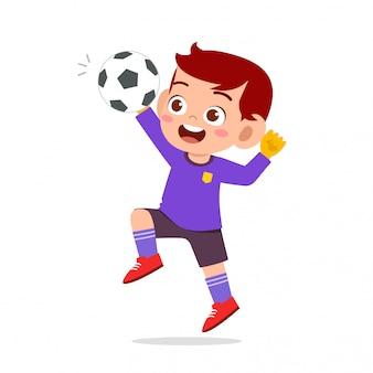 Szczęśliwy chłopiec dziecko grać w piłkę nożną jako bramkarz