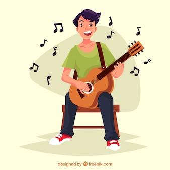 Szczęśliwy chłopiec gra na gitarze