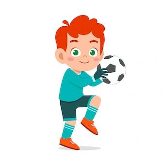 Szczęśliwy chłopiec gra w piłkę nożną jako bramkarz