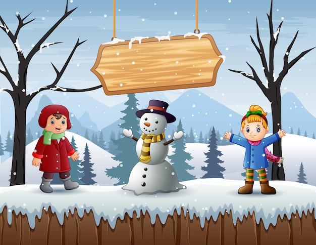 Szczęśliwy chłopiec i dziewczynka stojąc z bałwana w zimie na zewnątrz