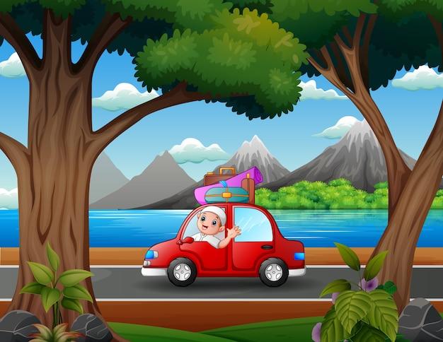 Szczęśliwy chłopiec muzułmański podróżujący z czerwonym samochodem
