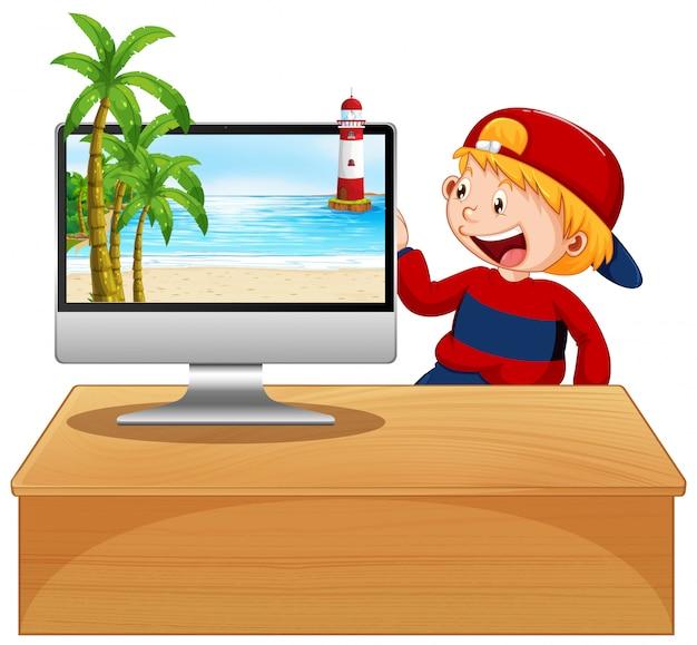 Szczęśliwy chłopiec obok komputera woth scena plaży na ekranie