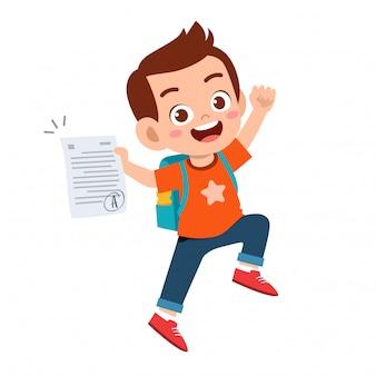 Szczęśliwy chłopiec słodkie dziecko ma dobry znak egzaminu