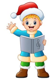 Szczęśliwy chłopiec śpiewa kolęda machać